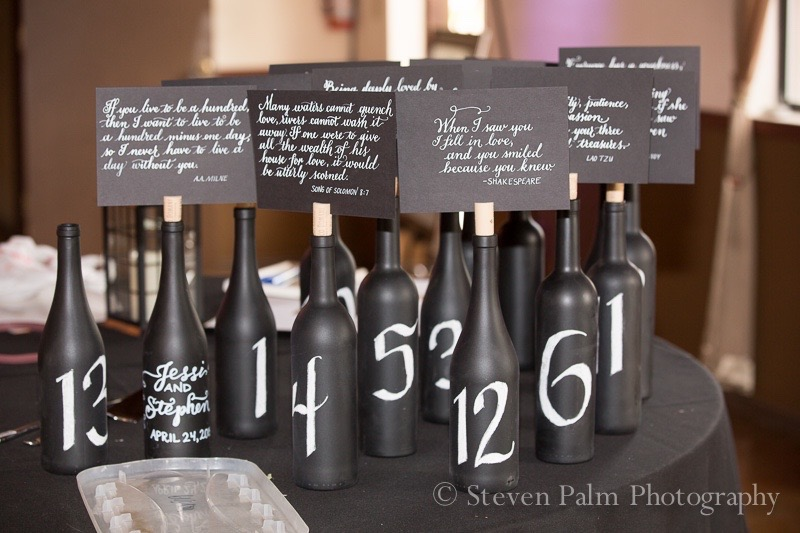 Wine bottles with handlettered numerals, each topped with a different poem written in calligraphy, served as the table numbers for this lovely outdoor wedding.