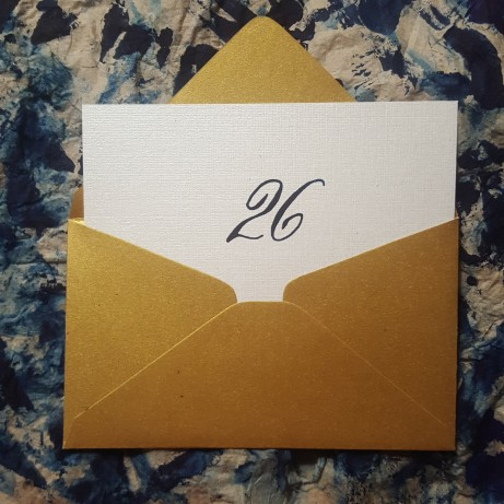 Table number 26 written on an escort card in Copperplate Script in navy blue gouache with a pointed flexible nib.