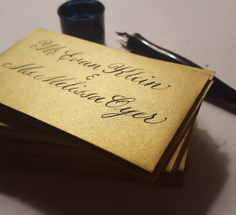 Stack of mini escort envelopes, each guest's name written by hand in calligraphy by Renee of Case Sensitive Designs LLC. Inside each envelope is a handlettered card with a corresponding table number.
