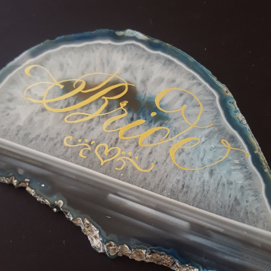 """Bride"" written in calligraphy in gold ink on an agate slice."
